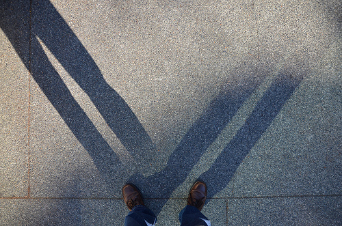 Photo of man with two shadows on the sidewalk indicating mixed signals